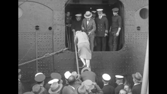 Man with Amelia Gade Corson climbs down from ship on ladder people waiting below on boat / Amelia follows him down ladder / Amelia standing in crowd...