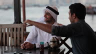 CU MS Man with Arab friend in outdoor restaurant/Dubai/UAE