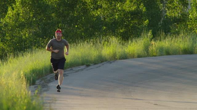 MS TD Man with artificial limb jogging on rural road / American Fork Canyon, Utah, USA
