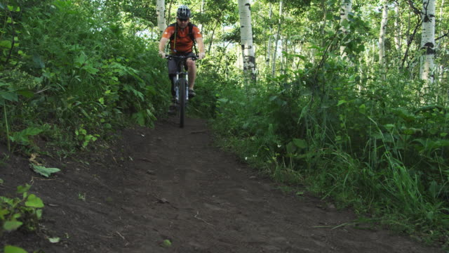MS PAN SLO MO Man with artificial limb riding mountain bike on forest trail / American Fork Canyon, Utah, USA