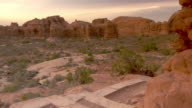 Man with backpack hiking past camera on high desert trail in Arches National Park