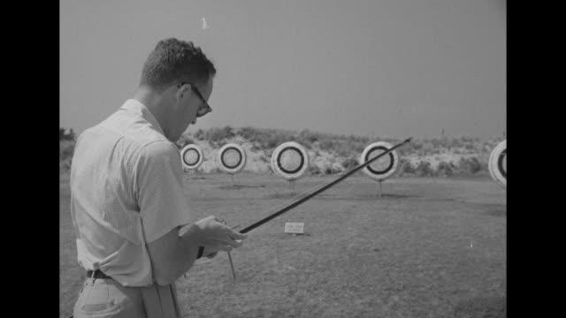 Man with bow shooting arrows at target / man putting golf ball on putting green / same man hitting golf ball onto green / CU arrow hitting target...