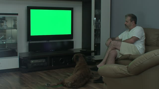Man with dog watches TV