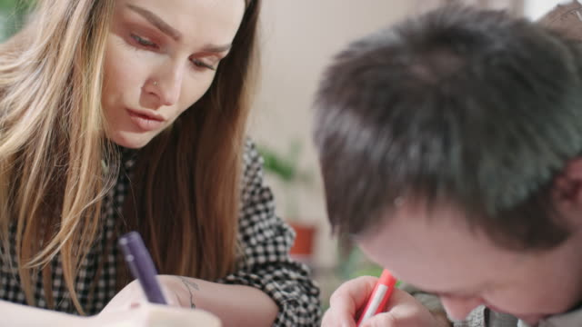 Man with Down syndrome and young woman drawing together