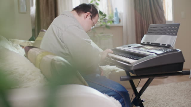 Man with Down syndrome playing piano at home