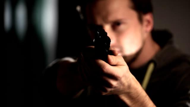 Mann mit Waffe Blick in die Kamera.
