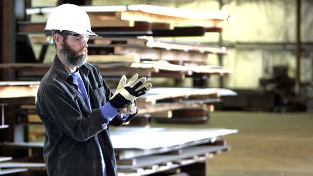 Mann mit Bauarbeiterhelm Schutzhandschuhe anziehen