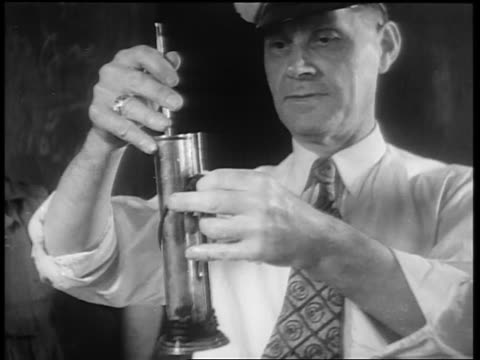 B/W 1932 man with hat testing whiskey with device / whiskey production / Louisville KY