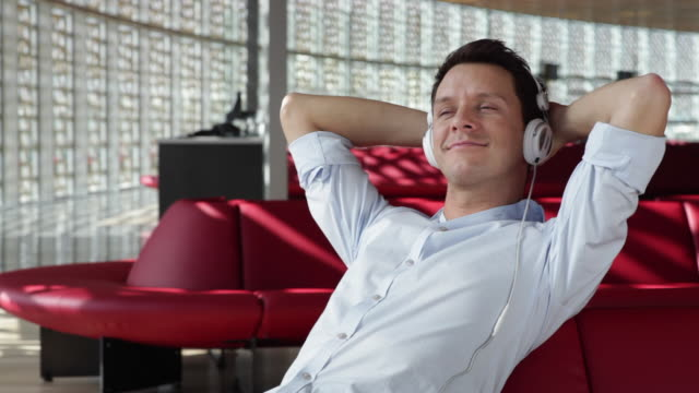 MS Man with headphones relaxing at departure lounge / Toulouse, Haute-Garonne, France