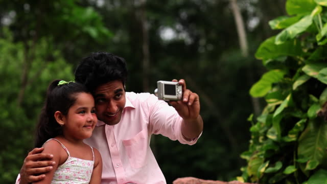 Man with his daughter taking picture with a digital camera