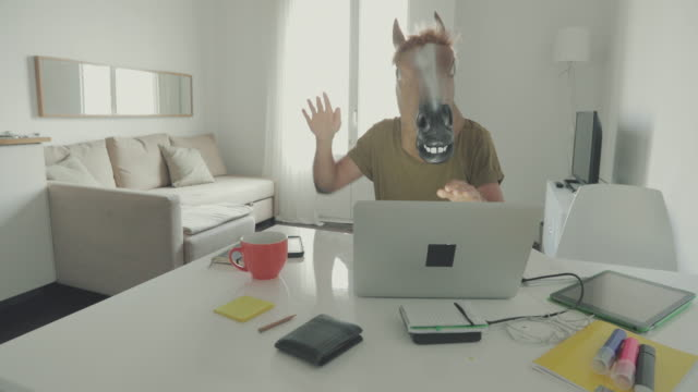 Man with horse head mask working at home