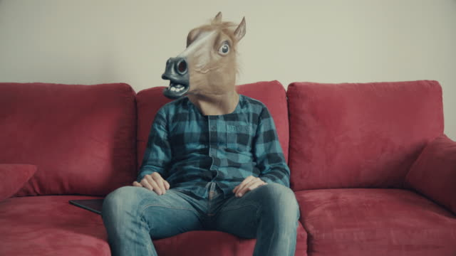 Man with horse head sitting on a red sofa
