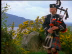 Man with kilt playing bagpipes marching off screen / Loch Ness in background / Inverness, Scotland