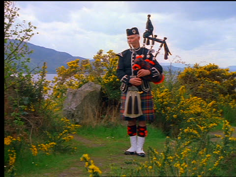 Man with kilt playing bagpipes near bushes / Loch Ness in background / Inverness, Scotland