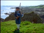 Man with kilt playing bagpipes near castle ruins / ocean in background / Newark Castle, Scotland