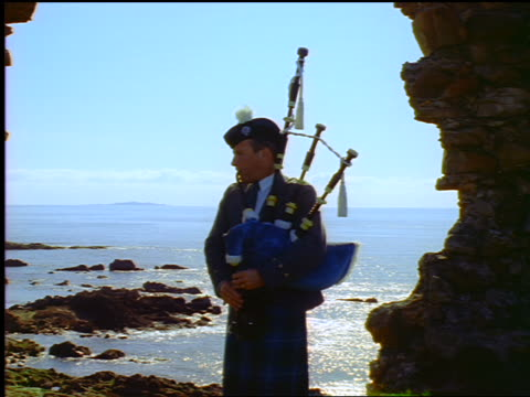 Man with kilt playing bagpipes under arch of castle ruins / ocean in background / Newark Castle, Scotland