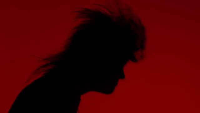 Man With Long Hair Head Banging in Super Slow Motion, with Strobe Lighting