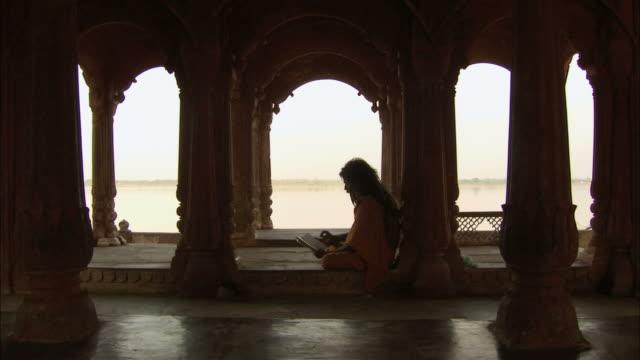 WS Man with long hair wearing robe prays in  temple / Varanasi, Uttar Pradesh, India