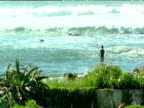 Man with long rod fishing from rocks waves rolling Casablanca