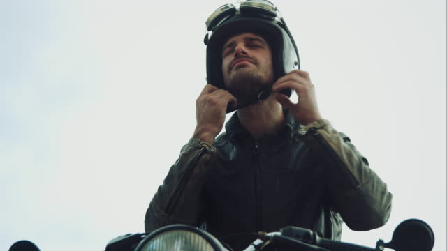 Man with motorcycle on a mountain road