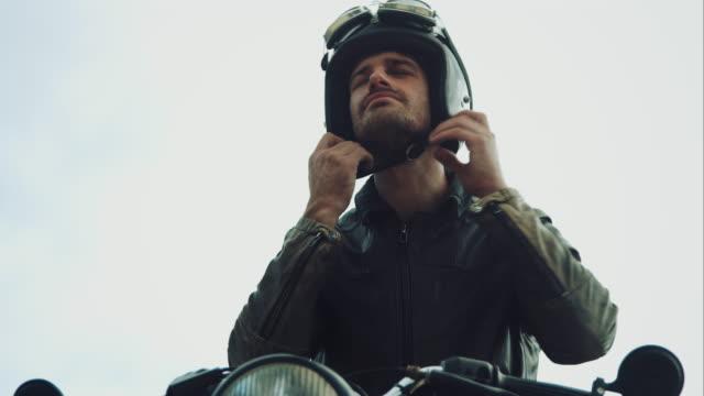 Uomo con una moto su una strada di montagna