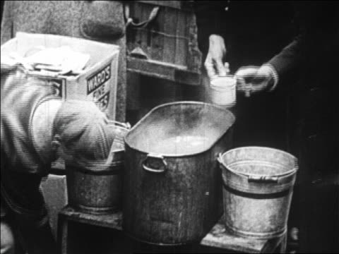 B/W 1929 man with mug being served food from bucket at outdoor soup kitchen / Depression / newsreel