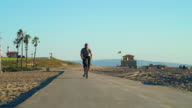 Man with prosthetic leg riding a bike at the beach