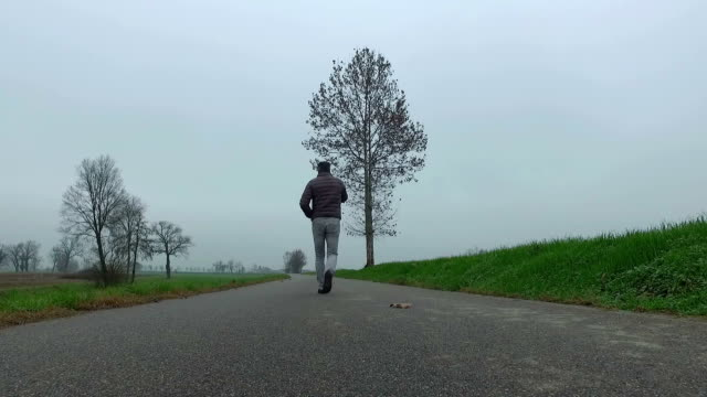 Man with smart phone walking on country road
