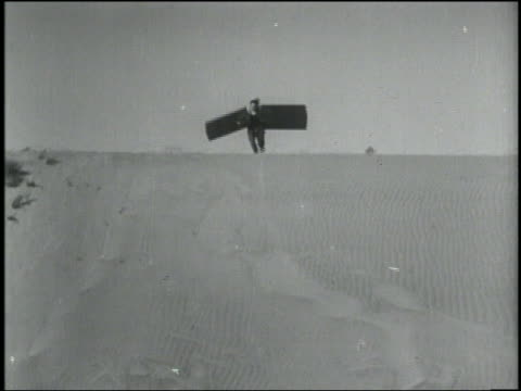 1934 B/W man (Hank Fadis) with square wings on arms jumps off sand dune + wipes out / Rowena, Oregon