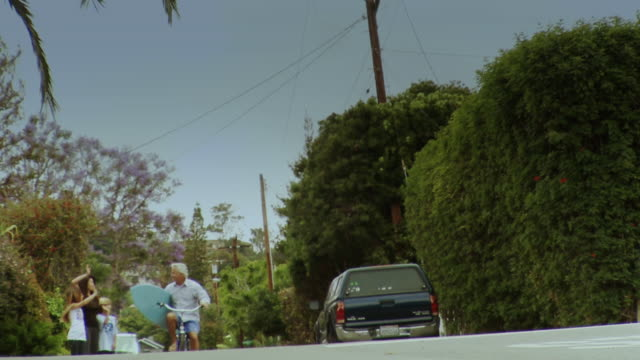 WS LA Man with surfboard riding bicycle, wife and children waving good-bye from side of street, Laguna Beach, California, USA