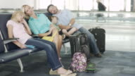 MS Man, woman, boy and girl sleeping on chairs in airport / Jacksonville, FL, United States