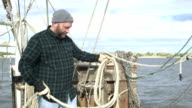Man working on commercial fishing boat coiling a rope