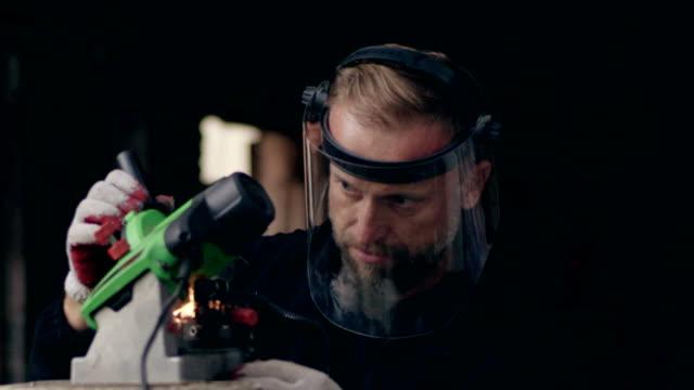 Mann mit Kettensäge Spitzer arbeitet. Nahaufnahme