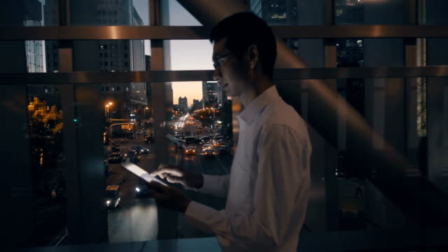 Man working with digital tablet at night
