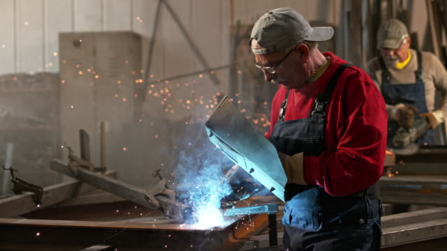 SLO MO DS Man working with welding torch in workshop