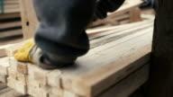Uomo al lavoro con legno a segheria