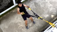 Man works out by using rope exercise training