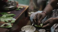 CU Man wrapping betel nuts in leaves / India