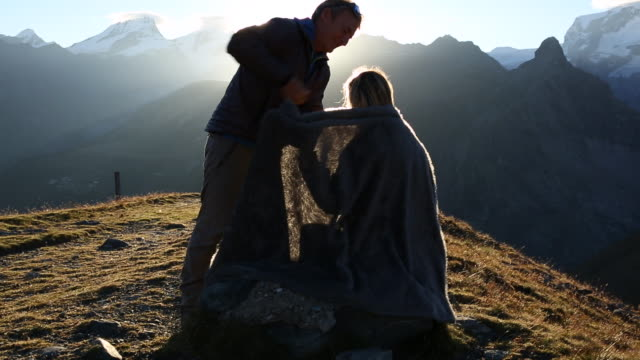 Man wraps blanket around woman, then watch sunrise over mtns.