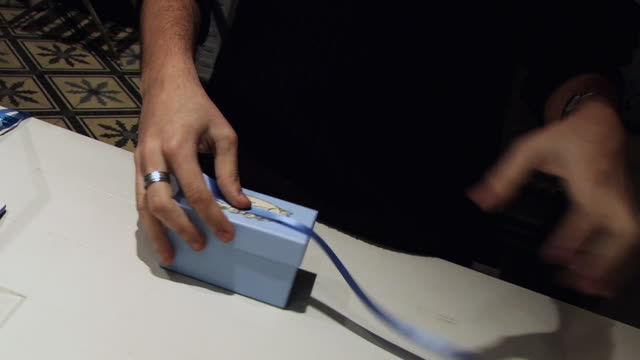 MS Man wraps blue box with blue ribbon / Paris, France