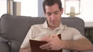 Man writing down notes in book
