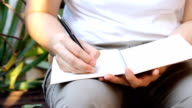 man writing on notebook paper - writing and literature concept