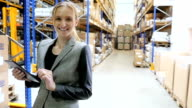 Manager smiling and holding tablet in warehouse