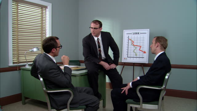 MS  Manager standing in front of Loss graph in with two businessmen in meeting/ Manager angrily gesturing for the men to get out of his office/ New York City