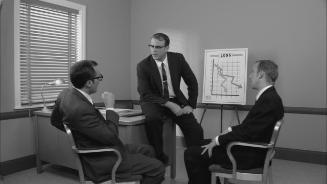 B/W MS Manager standing in front of Loss graph in with two businessmen in meeting/ Manager angrily gesturing for the men to get out of his office/ New York City