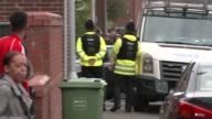 Police raid in Moss Side Various of police officers armed police officers and police vehicles on the streets and talking to local residents during a...