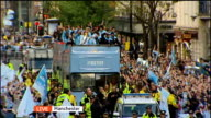 Manchester City victory parade following Premier League win LIVE reporter looking down road ZOOM IN opentop bus with players holding Premier League...