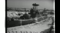 Manchurian troops pick ice away from a trapped Manchukuo naval ship in the frozen Amur River