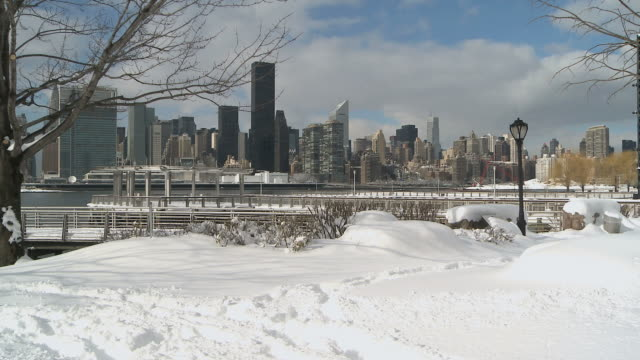 WS Manhattan skyline from snowy bank of East River / New York City, New York, USA