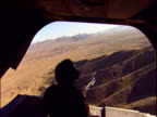 Manned machine gun looking out of back of Royal Marines Chinook helicopter flying over mountainous landscape War in Afghanistan 2001